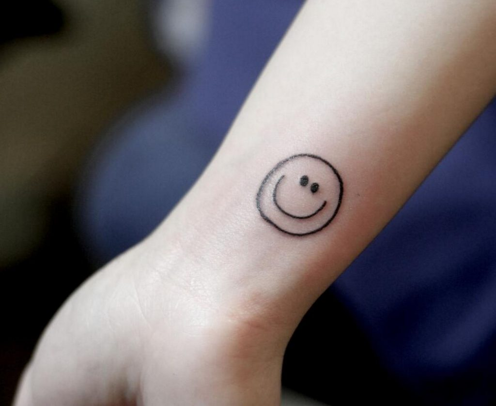 Smiley face tattoo on arm