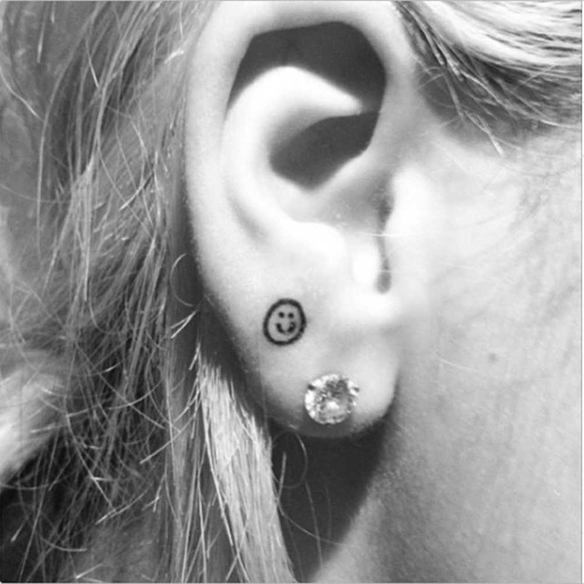 Smiley face tattoo on ear