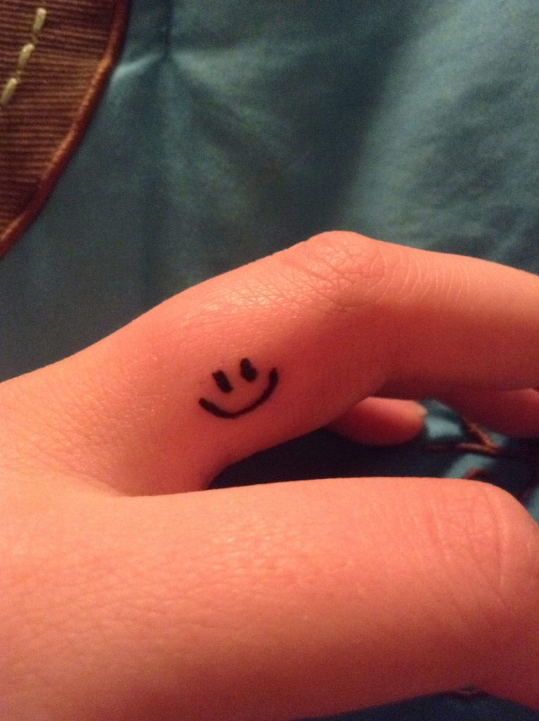 Smiley face tattoo on finger