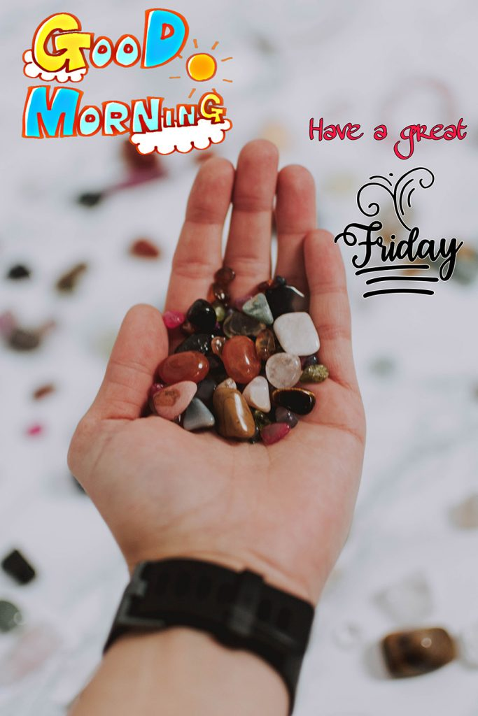 Good morning friday image with hand holding colorful pebbles